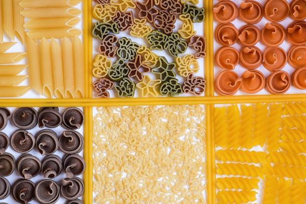 Rohe nudeln und spaghetti in verschiedenen farben und sorten werden in quadratischen zellen ausgelegt.