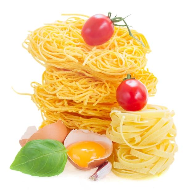 Rohe nudeln von tonarelli und tagliatelle mit ei und tomate isoliert auf weiß