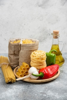 Rohe nudelsorten mit knoblauch, chilischoten und olivenöl.