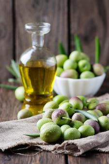 Rohe oliven für die herstellung von öl auf dem holztisch, selektiver fokus