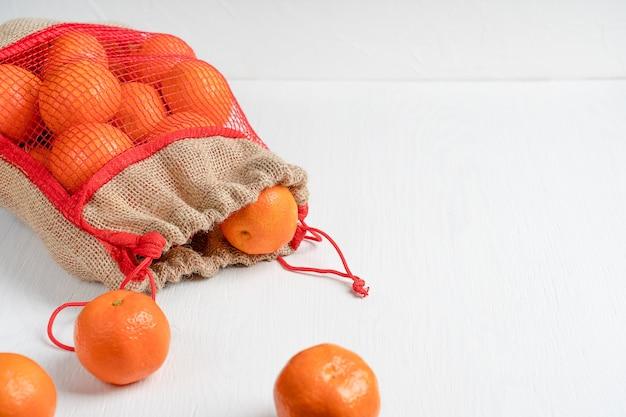 Rohe orange mandarinen oder mandarinen, die im leinwandnetzbeutel auf weißem holztisch bei küche legen