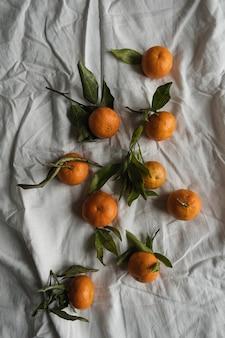 Rohe orangen, mandarinen auf zerknittertem tuch. frisches gesundes obst
