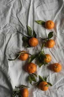 Rohe orangen, mandarinen auf zerknittertem tuch
