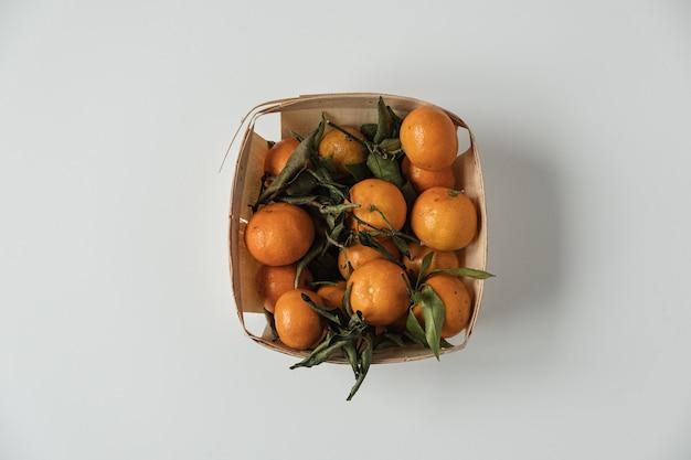 Rohe orangen, mandarinen mit grünen blättern im korb auf weiß