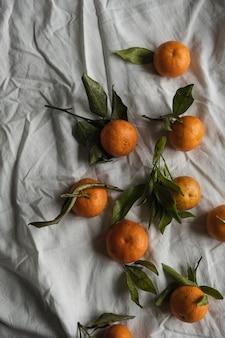 Rohe orangen, mandarinenfrüchte mit grünen blättern auf grauem zerknittertem leinentuch