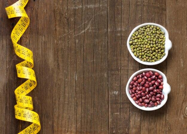 Rohe organische azuki und mungobohnen mit maßband auf holztischoberansicht mit kopienraum