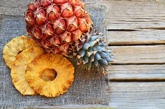Rohe organische getrocknete ananasscheiben und frische reife ananas tragen auf hölzerner rustikaler tabelle früchte.