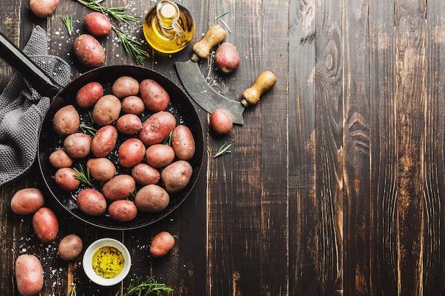 Rohe organische kartoffeln mit gewürzen auf holztisch