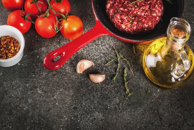 Rohe organische rindfleischfleisch-burgerkoteletts mit gewürzen, thymian, tomaten, olivenöl in der bratpfanne auf schwarzem, draufsicht copyspace