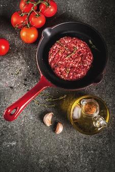 Rohe organische rindfleischfleisch-burgerkoteletts mit gewürzen, thymian, tomaten, olivenöl in der bratpfanne auf schwarzer, draufsicht