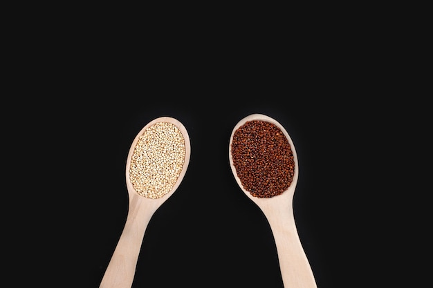 Rohe organische rote und weiße quinoa-körner in holzlöffeln auf schwarzem hintergrund
