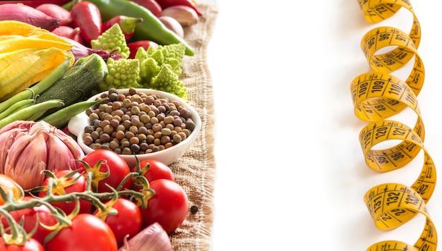 Rohe organische roveja-bohnen und rohes gemüse mit maßband lokalisiert auf weißer nahaufnahme