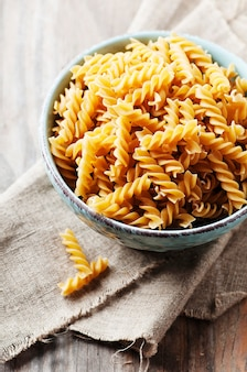 Rohe pasta fusilli in schüssel mit textil