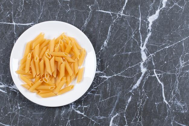 Rohe pasta penne auf weißem teller. draufsicht.
