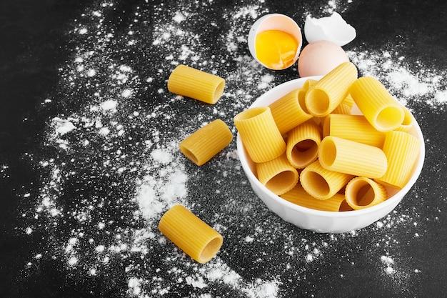 Rohe pasta penne in einer weißen tasse.