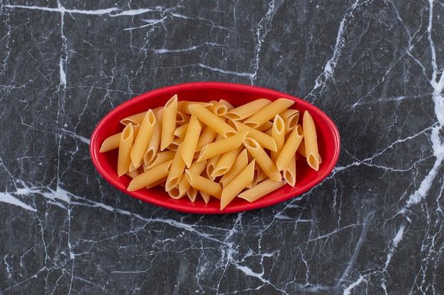 Rohe penne pasta in der roten schüssel über schwarz.