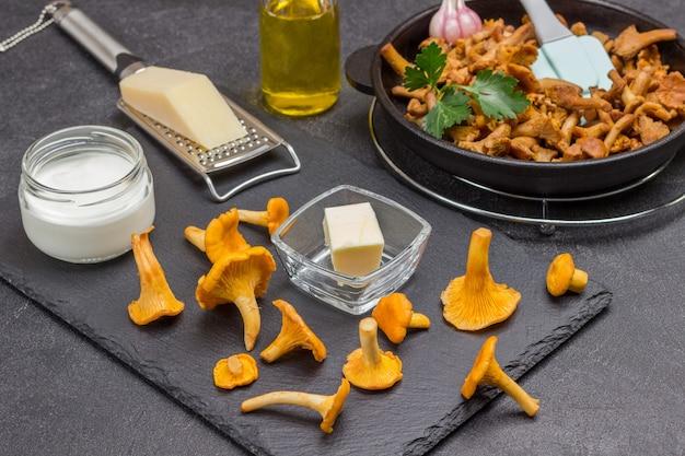 Rohe pfifferlinge, butter, geriebener käse. gebratene pfifferlinge in der pfanne. schwarzer hintergrund. ansicht von oben