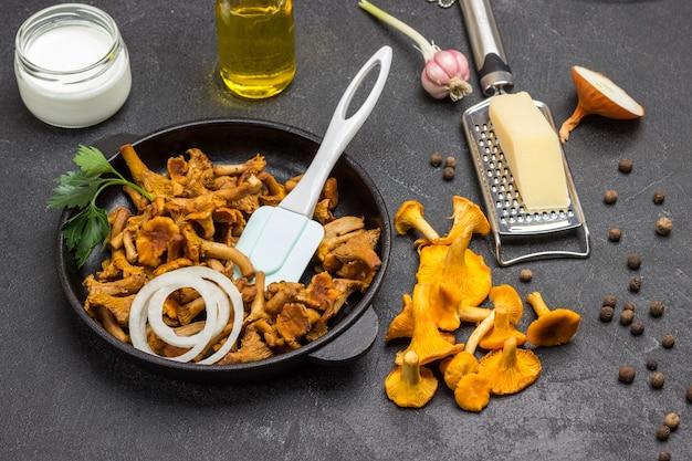 Rohe pfifferlinge, öl in der flasche und käse auf dem tisch. gebratene pfifferlinge, spatel und gehackte zwiebel in der pfanne. schwarzer hintergrund.