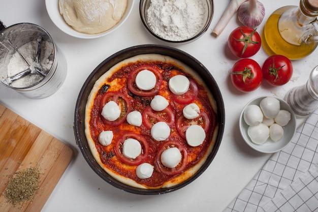 Rohe pizza margarita mit bestandteilen.