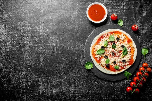 Rohe pizza mit kirschtomaten, käse, oliven und spinat. auf dunklem rustikalem hintergrund