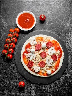 Rohe pizza mit tomatenmark, käse und würstchen. auf dunklem rustikalem hintergrund
