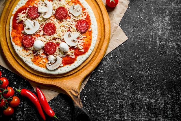Rohe pizza mit tomatenmark, pilzen und würstchen auf dunklem rustikalem tisch