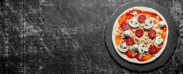Rohe pizza mit würstchen und pilzen auf einem steinbrett. auf dunklem rustikalem hintergrund