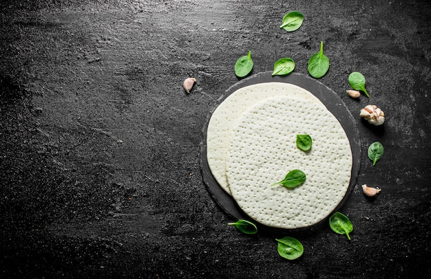 Rohe pizza. rundteig mit spinat und knoblauch ausgerollt. auf schwarzem rustikalem hintergrund