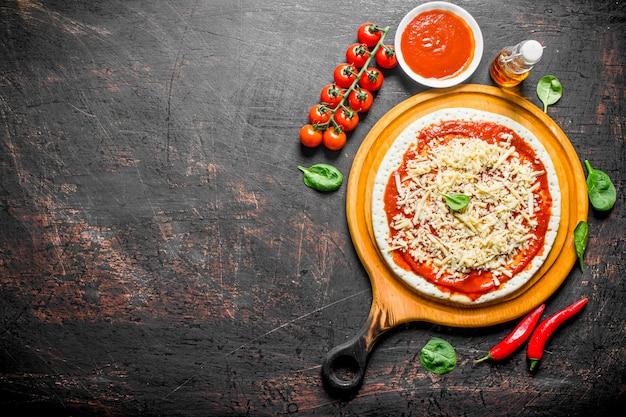 Rohe pizza. teig für hausgemachte pizza ausgerollt. auf dunklem rustikalem hintergrund