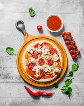 Rohe pizza. teig mit würstchen, käse, tomatenmark und spinat ausrollen. auf weißem hölzernem hintergrund
