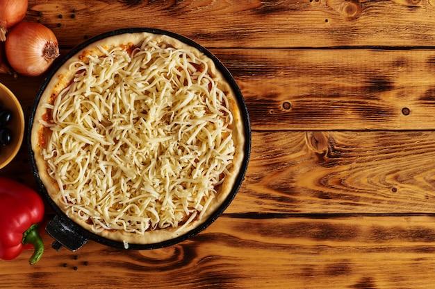 Rohe pizza-zutaten auf holztisch mit kopienraum. draufsicht. rustikal