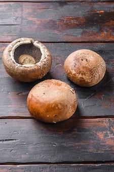 Rohe portobello-pilze, die auf seitenansicht des dunklen alten holztischs gesetzt werden.