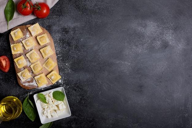 Rohe ravioli mit basilikum, käse und tomaten auf schwarzem hintergrund