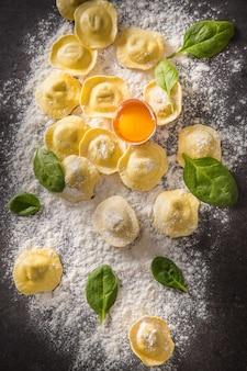 Rohe ravioli mit mehl-ei-pilzen und und spinat - ansicht von oben. italienische oder mediterrane gesunde küche.