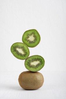 Rohe reife grüne kiwi-fruchtscheiben, die auf weißem holztisch übereinander balancieren