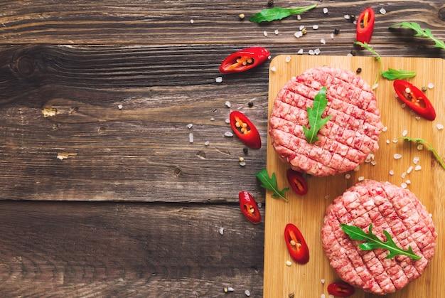 Rohe rinderhackfleischburger mit chili-pfeffer und rucola auf rustikalem holz