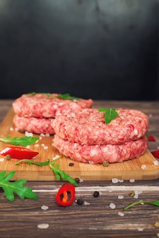 Rohe rinderhackfleischburger mit chili-pfeffer und rucola auf rustikalem holztisch