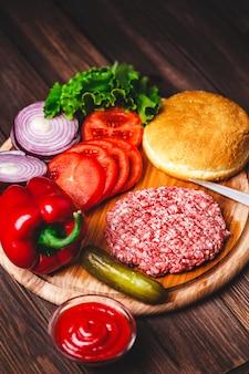 Rohe rinderhackfleischfleisch burger-steakkoteletts mit gewürz, käse, tomaten, salat und brötchen auf hölzernen brettern der weinlese