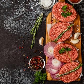 Rohe rinderhackfleischsteakkoteletts mit kräutern und gewürzen.