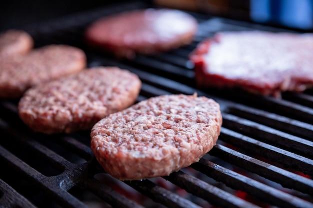 Rohe rindfleischburger mit einer prise salz und schwarzem pfeffer auf dem grill. zubereitetes fleisch zum grillen. rote burger schnitzel. runde pastetchen aus rohem hackfleisch, geröstet auf einem metallgitter.