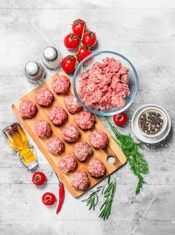 Rohe rindfleischfleischbällchen mit gewürzen und duftendem dill auf einem rustikalen tisch.