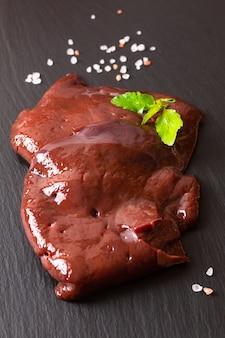 Rohe rindfleischleber der organischen neuen scheibe des lebensmittelkonzeptes auf schwarzem schieferbrett