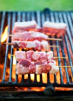 Rohe rindfleischspieße, die über einem grillfeuer grillen