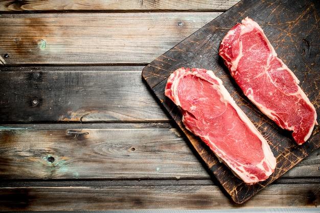 Rohe rindfleischsteaks auf schneidebrett auf holztisch.