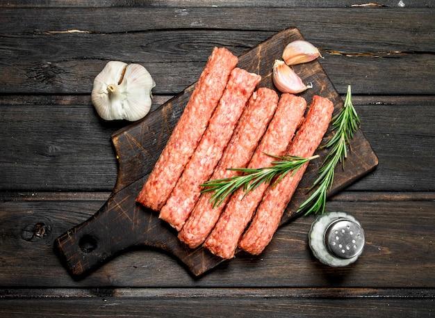 Rohe rindfleischwürste mit gewürzen und kräutern. auf einem holz.