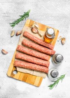 Rohe rindfleischwürste mit gewürzen und olivenöl. auf einer rustikalen oberfläche.