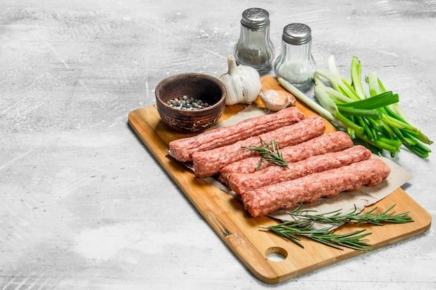 Rohe rindfleischwürste mit knoblauch und kräutern. auf einer rustikalen oberfläche.