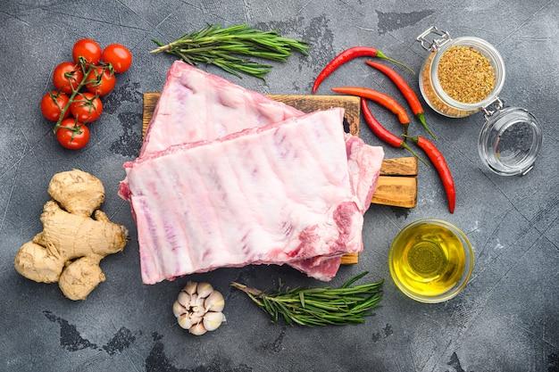 Rohe rippen mit rosmarin und gemüse, auf grauem tisch, draufsicht flach gelegt