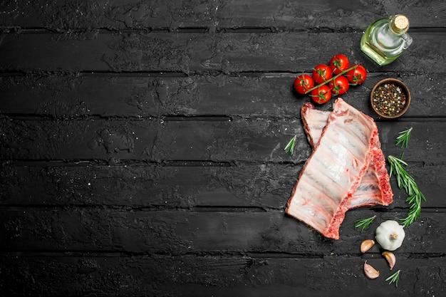 Rohe rippen mit tomaten und gewürzen auf dunklem rustikalem tisch.