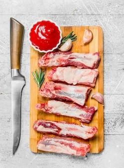 Rohe rippen mit tomatensauce und duftendem rosmarin. auf einem rustikalen hintergrund.